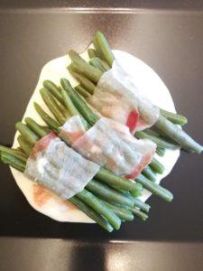 Rotolini di fagiolini ripieni avvolti in pancetta su salsa di gorgonzola